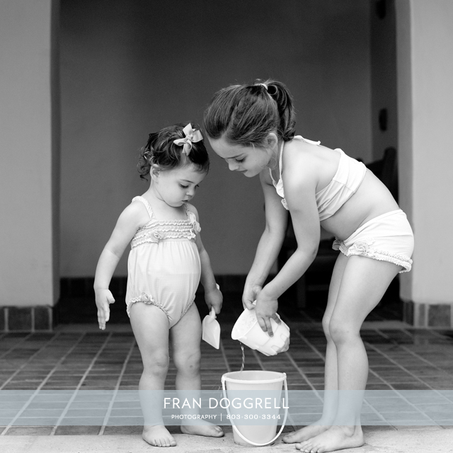 Fran Dogrell timeless portrait of two young girls enjoying their day in the sun with their toy bucket.