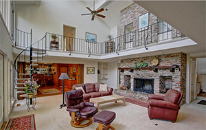 Circling the stone fireplace and descending in either direction from the foyer is the spacious three story family room.